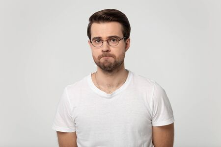 Millennial guy wearing glasses feels upset frustrated or offended with pursed lips posing isolated on gray studio background, lack of self-esteem, guilty made mistake, nervous tension, mess up concept Stock Photo