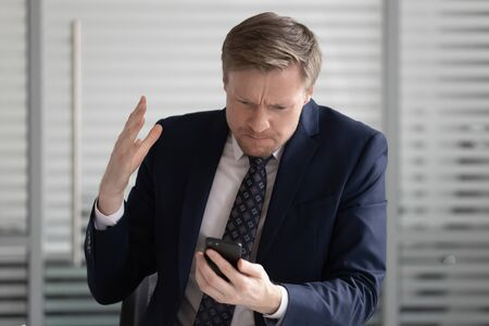 Angry stressed business man wear suit frustrated with broken stuck smartphone in office holding using texting on phone annoyed with missed call, outraged having problem bad complaint on cellphone