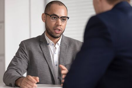 Serious african american bank investment advisor insurance broker lawyer in suit consulting client customer at business advice meeting talking to male customer explaining business loan deal benefits. 写真素材
