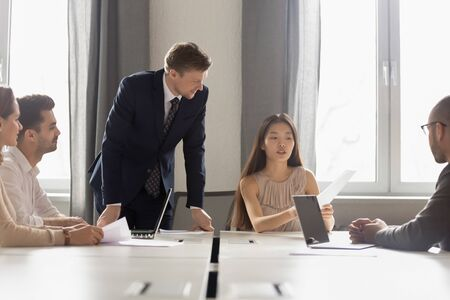 Asian female employee presenting report to boss at diverse group meeting, focused korean worker holding papers talking about work results, chinese manager consulting clients colleagues at briefing