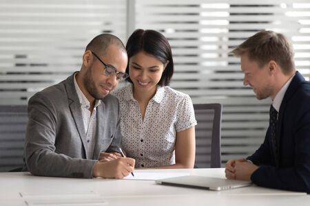 Happy proud mixed ethnicity young family couple customers sign loan investment contract sale purchase prenup agreement meeting bank manager agent make financial mortgage deal buying house insurance. Stock Photo