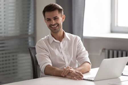 Cheerful young business man laughing sitting at work desk, happy male professional smiling looking away having fun at workplace with laptop, worker express positivity enjoy funny moments in office Stock fotó