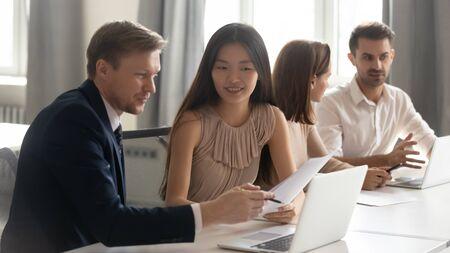 Kaukasischer männlicher Manager-Mentor unterrichtet asiatische weibliche Kundenpraktikantin über Vertrags-Online-Projekt mit Blick auf Laptop am Schreibtisch im Büro sitzen, glückliche koreanische Auszubildende lernen neue Fähigkeiten Standard-Bild