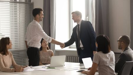Smiling male business partners negotiators handshake start group office negotiation, company representatives welcoming shake hands at meeting getting acquainted expressing respect make financial deal