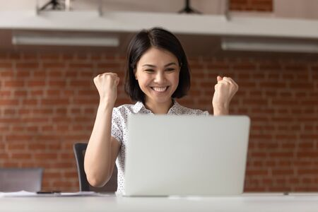 Overjoyed euphoric asian business woman worker feel winner celebrate online win looking at laptop computer, happy chinese student excited with great internet success professional triumph opportunity