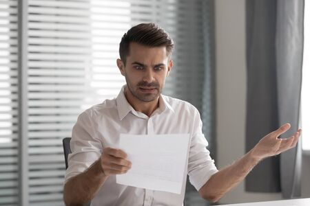 Shocked frustrated business man read bad news in paper mail letter got fired feel stressed confused about money problem bank debt notification rejection mad about bill tax invoice sit at office desk. Foto de archivo