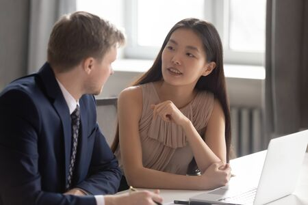 Two diverse colleagues working together talking sit at office desk with laptop, asian business woman intern trainee listening to caucasian male manager mentor instructing during corporate discussion Stock Photo