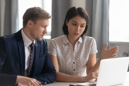 Female asian bank manager broker mentor teacher consult caucasian male client teaching intern using laptop showing online presentation explain deal benefits talk convince customer at business meeting. Stock Photo