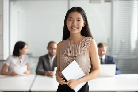 Smiling young asian business woman holding digital tablet looking at camera, happy korean coach intern employee professional corporate manager posing in office, millennial female team leader portrait Stock Photo