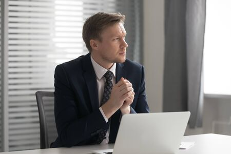 Serious thoughtful businessman wear suit sit at office desk with laptop feel doubtful concerned about business challenge, pensive anxious ceo looking away thinking solving work problem at workplace