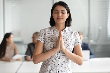 Happy grateful asian business woman meditating praying with hope standing in office with eyes closed put hands together in prayer, mindful religious chinese employee make wish feeling gratitude Stock Photo