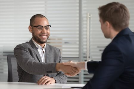 Smiling successful male african american job applicant shake hand of hr employer get hired employed at interview, happy mixed race bank manager broker handshake client customer at business meeting Stock fotó