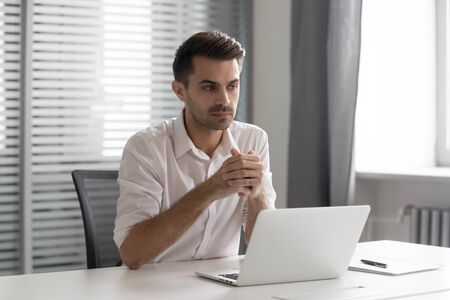 Thoughtful businessman lost in thoughts at workplace, pensive professional think of problem solution sit at work desk with laptop, serious executive search new idea solve business challenge in office