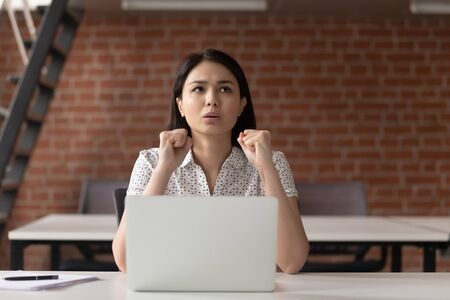 Stressed nervous asian business woman clenching fists concerned about problem in office, anxious tensed japanese woman in trouble panic looking worried scared afraid of failure hoping for solution