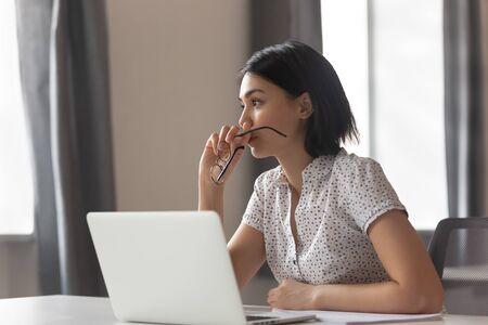 Mujer de negocios asiática ansiosa pensativa mirando a otro lado pensando en resolver problemas en el trabajo, preocupada mujer china joven seria preocupada por tomar una decisión difícil perdida en sus pensamientos reflejando sentarse con la computadora portátil