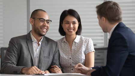 Happy young mixed ethnicity family couple customers listening to bank manager broker insurer consulting clients explaining mortgage investment insurance real estate deal benefits at business meeting.