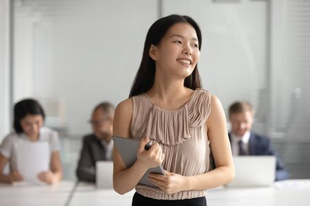 Happy dreamy young asian businesswoman holding digital tablet looking away dream of successful career, plan new goals, think about future hope for new opportunities in office, business vision concept