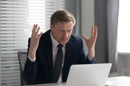 Annoyed mad businessman wearing suit frustrated with online problem, angry stressed male professional using laptop outraged by broken pc, crazy about stuck slow computer virus app error at workplace Stockfoto