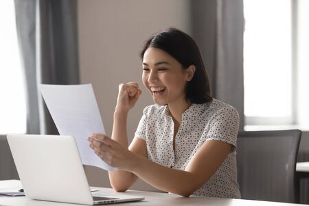 Felice donna d'affari asiatica celebra il successo grande risultato risultato del lavoro guarda il rapporto finanziario, entusiasta studente giapponese vincitore legge buone notizie in una lettera cartacea felicissima per la borsa di studio di ammissione
