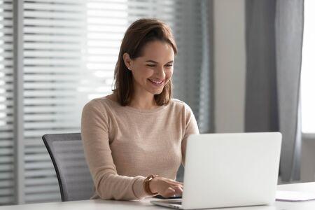 Glückliche junge Geschäftsfrau, die am Computer arbeitet und im Internet chattet, um am Arbeitsplatz online zu kommunizieren, lächelnde Unternehmerin, die E-Mails auf dem Laptop schreibt, sitzen am Schreibtisch