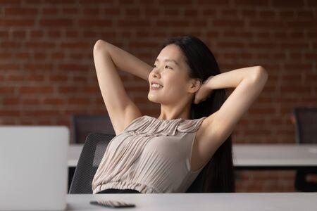 Fröhliche positive Ruhe asiatische Geschäftsfrau Angestellte Studentin entspannen Sie sich bei der Arbeit, halten Sie die Hand hinter dem Kopf, sitzen Sie am Schreibtisch, ruhen Sie sich vom Computer aus, fühlen Sie sich nicht stressabbauend am Arbeitsplatz.