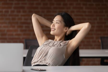 Happy positive calm asian business woman employee student relax take break at work hold hand behind head sit at office desk rest from computer stretch feel no stress relief peace of mind at workplace. Stockfoto