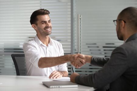 Happy successful male job applicant manager get hired handshaking hr employer client at job interview, diverse businessmen shake hands make business deal agreement at meeting express trust respect