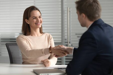 Happy successful female job applicant get hired employed at job interview negotiations, smiling manager candidate handshake hr customer make business deal with client, recruit and employment concept Stock Photo
