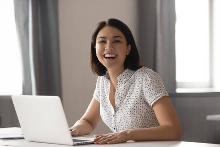 Happy asian business woman laughing sitting at work desk with laptop, cheerful smiling female chinese employee having fun feeling joy and positive emotion express sincere laughter at office workplace