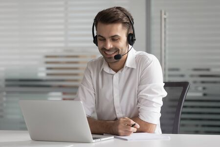 Smiling business man wearing wireless headset make conference video call looking at laptop screen, happy salesman customer service support agent helpline representative talk by online chat in office