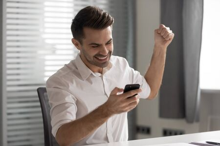 Overjoyed excited young businessman winner receive good news in mobile message use smart phone feel happy, motivated euphoric man look on cellphone celebrate mobile success bet win victory in office Stok Fotoğraf