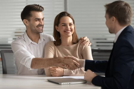 Happy young couple handshake lawyer broker make financial business deal, smiling satisfied family shake hand of realtor insurer thanking for consulting buying insurance services at meeting