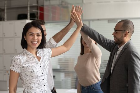 Excited happy asian business woman team leader coach give high five to colleagues looking at camera, motivated office workers celebrate reward success good teamwork result engaged in teambuilding 免版税图像