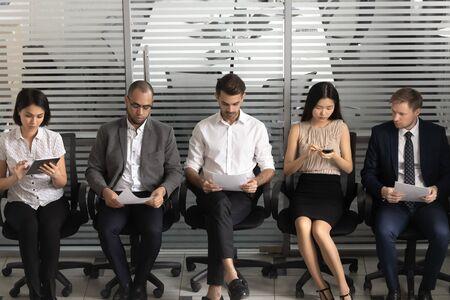 Des gens d'affaires de divers candidats ciblés sont assis sur des chaises dans une file d'attente dans la salle d'attente, des candidats multiculturels se préparent à un entretien d'embauche avec des appareils de CV, un concept de ressources humaines