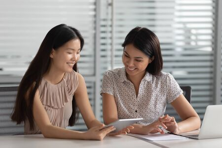 Smiling female korean mentor manager helping asian colleague intern client using digital tablet showing online presentation teaching new worker trainee discuss online project in office, apprentice Stock Photo