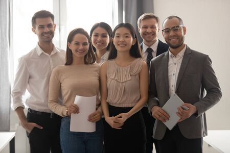 Multicultural professional work team happy company employees group looking at camera stand in office, smiling diverse corporate staff workers business people posing together, human resource portrait Stock Photo