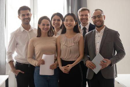 Multikulturelles professionelles Arbeitsteam glückliche Unternehmensmitarbeitergruppe mit Blick auf den Kamerastand im Büro, lächelnde verschiedene Unternehmensmitarbeiter, Geschäftsleute, die zusammen posieren, Human Resource Portrait