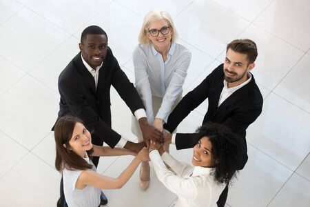 Smiling excited diverse team employees stack pile of hands top view, motivated for business success office workers involved in team building activity, staff training briefing, show unity at work