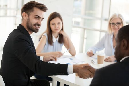Confident businessman shaking hand African American colleague at company meeting in boardroom, employee greeting, introducing or getting acquainted business partner in office, congratulate, close up