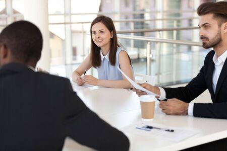 Interested employees sitting at briefing in boardroom, listen to African American colleague talking, multiethnic workers discussing business strategy, new project at company meeting, share ideas 写真素材 - 127862005