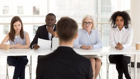 Diverse HR managers listen to male applicant answering questions rear view, team recruiters making decision, thinking, looking at job seeker, candidate for vacancy introducing, employment concept 写真素材