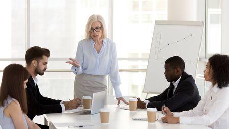 Empresaria madura enojada, jefe de mediana edad regaña, culpa a los empleados por los malos resultados del trabajo, realiza reuniones informativas de negocios, da conferencias al equipo de trabajadores de oficina, subordinados por fallas comerciales en una reunión de la empresa