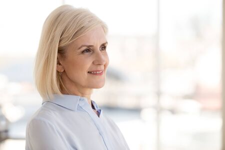 Smiling thoughtful mature businesswoman thinking about work opportunities, business strategy, looking at distance, female employee dreaming about successful future, business vision concept, close up Stockfoto