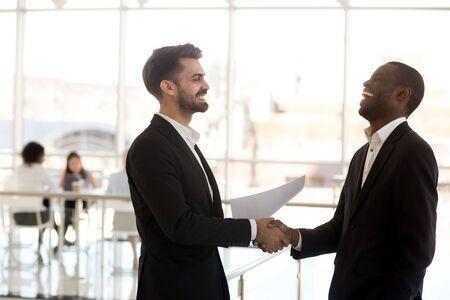 ジョークの同僚の握手を笑う多様な、会社のオフィスの廊下で会う、面白い会話をしている従業員、握手をする多民族ビジネスマン、挨拶、休憩中に話す