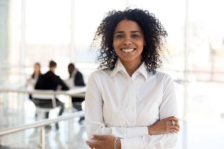 Kopfschussporträt lächelnde afroamerikanische Geschäftsfrau im Firmenflur, glückliche schwarze Mitarbeiterin, die Foto am Arbeitsplatz macht, Kamera anschaut, selbstbewusste Arbeiterin mit verschränkten Armen