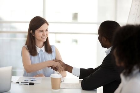Happy young businesswoman shake hand of African American colleague at company meeting, introducing, greeting or getting acquainted business partner at briefing, congratulating with promotion