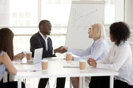 African American businessman shake hand of mature female colleague at business briefing in boardroom, boss congratulate worker, black employee greeting or getting acquainted partner at company meeting Stockfoto