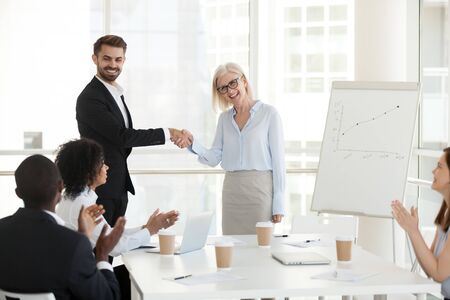 Smiling confident businessman shaking hand of excited mature businesswoman at company meeting, boss congratulate subordinate with promotion or employment, diverse colleagues applaud successful worker