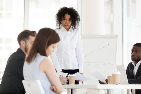 Angry African American businesswoman, boss scolding female young worker, intern for bad work results, holding business briefing, lecturing employee, subordinate for business failure at company meeting Фото со стока - 127862219
