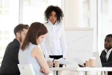 Wütende afroamerikanische Geschäftsfrau, Chefin, die weibliche junge Arbeiterin schimpft, Praktikantin für schlechte Arbeitsergebnisse, Geschäftsbesprechung abhalten, Angestellte belehren, Untergebene für Geschäftsversagen bei Firmenversammlung